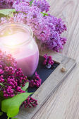 Fresh lilac flowers with candle — Stock Photo