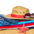Sunbathing accessories and straw hat on sand — Foto de Stock