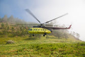 Large helicopter lands in the forest in the fog. — Stockfoto