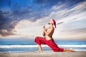 Christmas yoga on the beach — Stock Photo