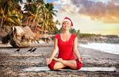 Christmas yoga on the beach — Stock Photo