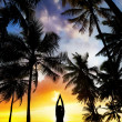 Stock Photo: Yogtree pose around palm trees