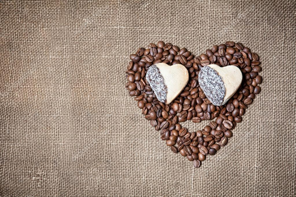 Funny face from coffee beans and cookies in shape of heart on textured sack. Free space for text — Stock Photo #18295563