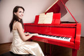 Woman playing the red grand piano — Stock Photo