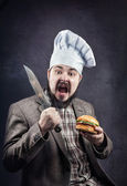 Cook with hamburger and knife — Stock fotografie