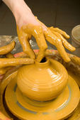 Hands of a potter, creating an earthen jar of red clay — Stock Photo