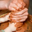 Stock Photo: Potters hands guiding pupil hands to help him to work with ceramic wheel