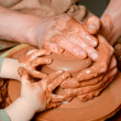 Potters hands guiding pupil hands to help him to work with ceramic wheel — Stock Photo #29599517