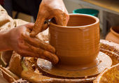 Hands of a potter, creating an earthen jar on the circle — Stockfoto