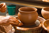 Hands of a potter, creating an earthen jar on the circle — Stock Photo