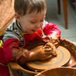 Stock Photo: A potters hands guiding pupil hands to help him to work with the ceramic wheel