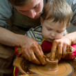 Potters hands guiding pupil hands to help him to work with ceramic wheel — Stock Photo #38772803