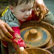 Potters hands guiding pupil hands to help him to work with ceramic wheel — Stock Photo #38772847