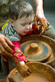 A potters hands guiding pupil hands to help him to work with the ceramic wheel — Stock Photo
