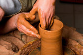 Hands of a potter, creating an earthen jar — ストック写真