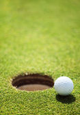 Golf ball on lip of cup — Stockfoto