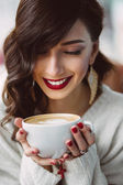 Young girl drinking coffee in a trendy cafe — Stock Photo