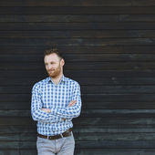 Portrait of young fashionable man against wooden wall — Stock Photo