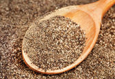 Ground black pepper (Piper nigrum) with wooden spoon — Stock Photo