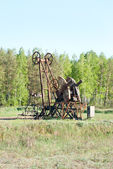 Old oil pump works on spring forest background — Stock Photo