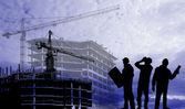 Silhouettes of builders on a background of houses under construction — Stock Photo