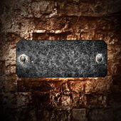 Grunge brick wall with a name sign — Stock Photo