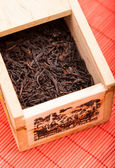 Box with black tea on red mat — Stock Photo