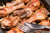 Baked chicken legs in tray on black wooden — Stock Photo