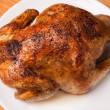 Roast chicken on white plate and wooden — Stock Photo