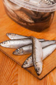 Salted anchovies in box on wooden — Stok fotoğraf