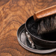 Container of shoe polish and brush on wooden — Stock Photo #20045115