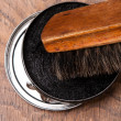 Container of shoe polish and brush on wooden — Stock Photo