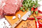Fresh meat of beef with bone on wooden spices and knife — Stock Photo