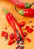 Cut capsicum chili pepper and peppercorn on wooden board — Stock Photo