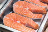 Raw salmon steaks on metal plate in shop-window — Stock Photo