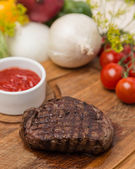 Hot grilled beef with garnish on wooden board — Stock Photo