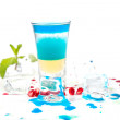 Short blue coctail with ice and color drops — Stock Photo #33329639