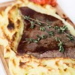 Stock Photo: Meat steak with potato puree backed on wood board