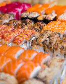 Assorted sushi and rolls on wood board in dark light — Stock Photo