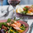 Foto Stock: Salad with salmon and verdure in plate on table with blue chair