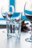 Glass with water and wineglasses on blue window background — Stock Photo