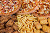 Fastfood chicken nuggets, legs, pizzas and fry potatos — Stock Photo