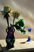 Vase with yellow roses and hourglass — Stock Photo