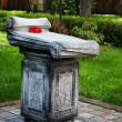 Old little monument in city park - Stock Photo