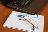 Glasses with notebook and pen near laptop — Stock Photo