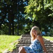 Beautiful pregnant woman in city park - Stock Photo