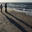 Royalty-Free Stock Photo: Two silhouettes of people on the beach