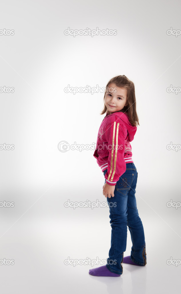 little girl in blue jeans and a red jacket in the studio