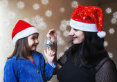 Mother and daughter in Christmas capsl — Stock Photo