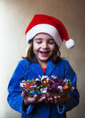 Girl in a christmas cap holds a dish with chocolates — Stock fotografie